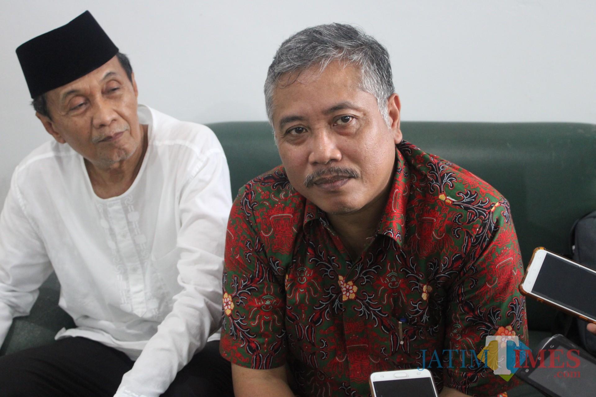 mengenakan kemeja batik berwarna merah, kuasa hukum yayasan Undar Jombang, Sholikin Rusli saat diwawancarai sejumlah awak media. (Foto : Adi Rosul / JombangTIMES)