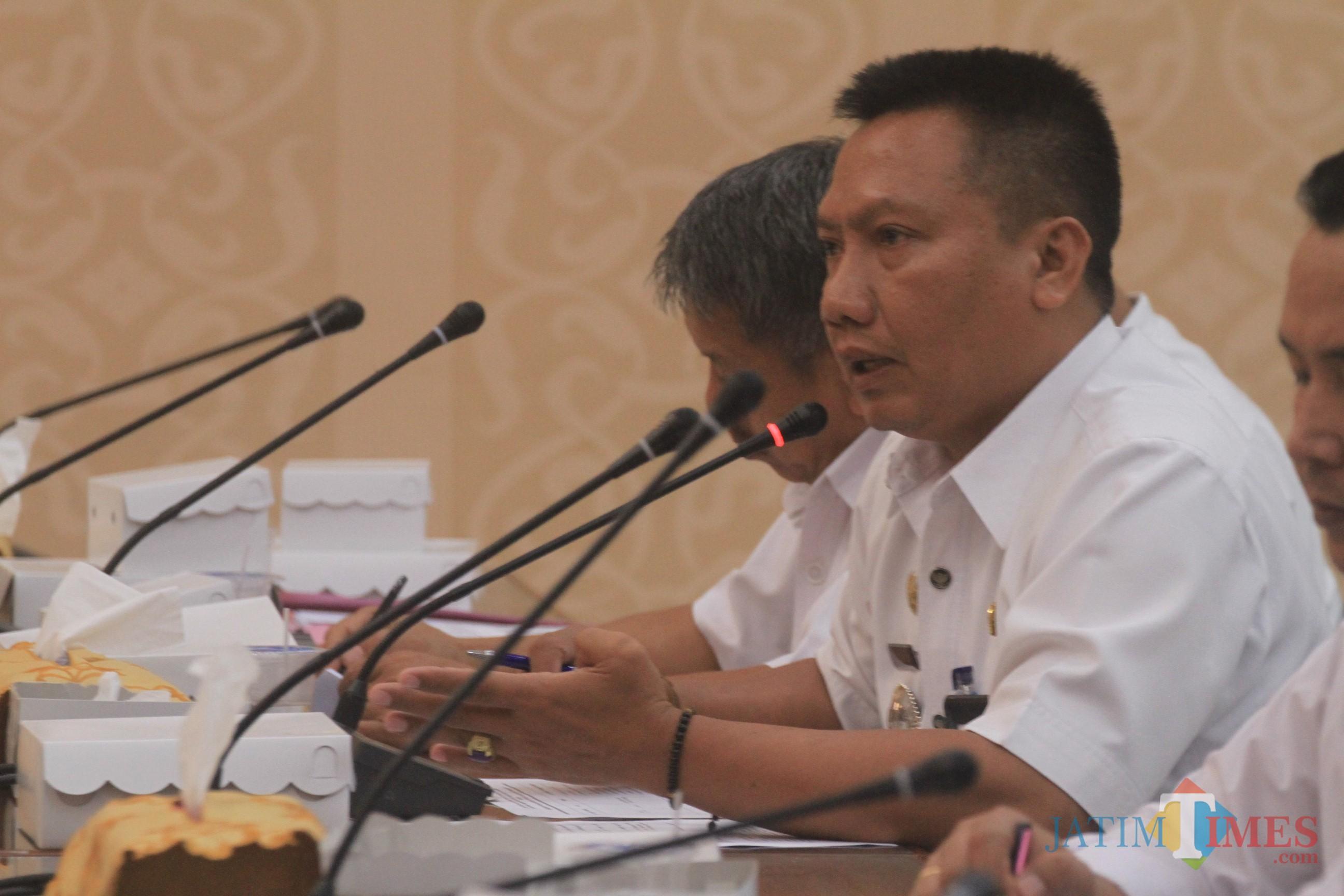 Camat Kedopok Imam Cahyadi saat menenyakan juklak dan juknis dana kelurahan pada rakor dengan komisi 1 (Agus Salam/Jatim TIMES)
