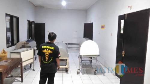 Petugas forensik sesaat setelah melakukan autopsi terhadap bayi yang dibuang dalam kloset (foto : Joko Pramono / Jatimtimes)