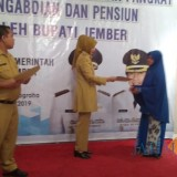 Bupati Jember dr Hj Faida MMR saat menyerahkan SK pensiunan kepada janda PNS. (foto : izza / Jatim TIMES)