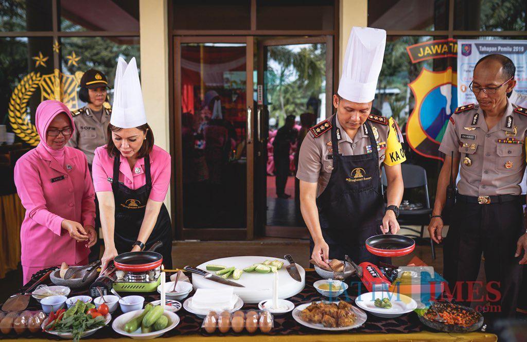 Kapolres Batu AKBP Hermanto (kanan) bersama Ketua Bhayangkari Kota Batu Enic Budi Hermanto saat memasak di halaman Polres Batu,�Senin (14/1/2019). (Foto: istimewa)