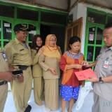 Kepala Dinsos Zainullah saat memberikan bantuan ke salah satu keluarga bayi tanpa anus di rumahnya (Agus Salam/Jatim TIMES)
