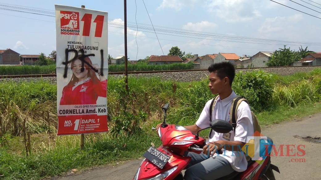Warga saat melintas di depan APK yang dirusak dengan menuliskan PKI (foto : Joko Pramono/Jatimtimes