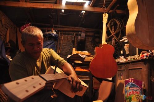 Fauzi saat sedang menghaluskan gitar buatannya.