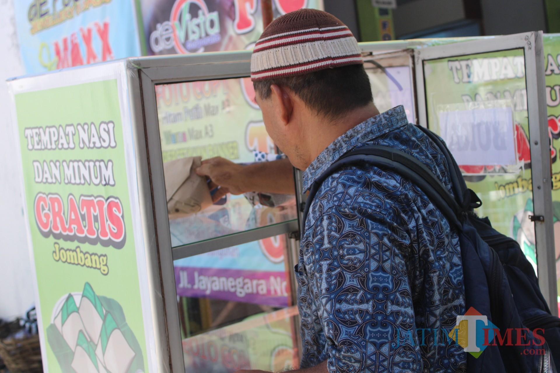 Salah satu warga yang melintasi Jl Jayanegara, Kelurahan Kepanjen, Kecamatan/Kabupaten Jombang, terlihat sedang mengambil makanan yang disediakan di gerobak tempat makanan dan minuman gratis. (Foto : Adi Rosul / JombangTIMES)