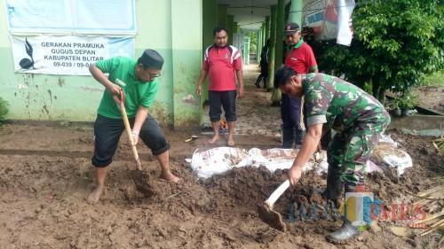 Anggota Koramil Bakung dan warga gotong royong bersihkan lumpur.(Foto : Team BlitarTIMES)