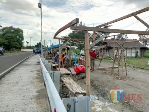 Pedagang membangun bangunan semi permanen di tepi jalan sekitar jembatan Ngujang 2 (foto : Joko Pramono/Jatim Times)