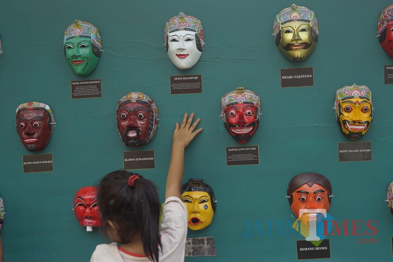 Seorang anak kecil yang bermain di sekitar display topeng. Foto : Agung Wardoyo untuk JatimTIMES