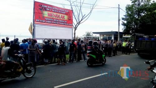 warga memasang baliho di dekat pintu masuk menuju area reklamasi