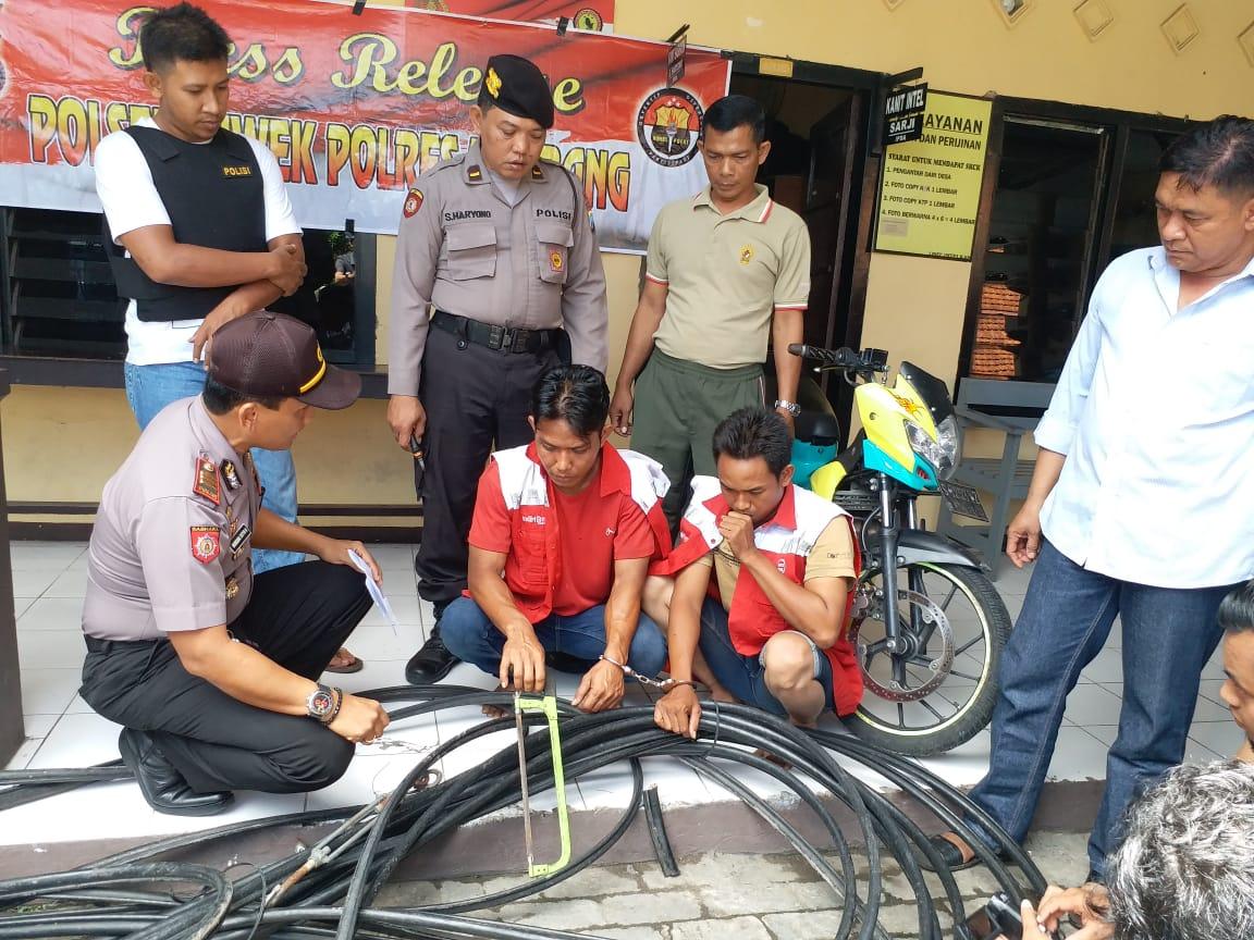 Kedua pelaku pencurian mempraktikkan aksi pencurian kabel di hadapan jajaran anggota Polsek Diwek. (istimewa)