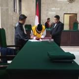 Terdakwa Gusti saat menandatangani vonis terhadap dirinya (foto : Joko Pramono/JatimTIMES)