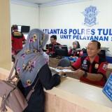 Petugas saat menyerahkan biodata pemohon SIM Ceria yang baru dicetak (foto : Joko Pramono/JatimTIMES)