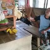 Ainamah, pemilik warung di dekat kandang ayam sedang menghalau lalat yang ada di warungnya