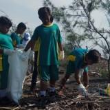 para pelajar SD sedang memungut sampah di kawasan pantai Cemara