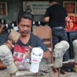 Supangat (50), pengerajin wayang potehi saat sedang mengerjakan salah satu karakter wayang di museum wayang potehi milik paguyuban Fu He An Gudo. (Foto : Adi Rosul / JombangTIMES)