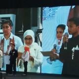 Ibu Negara Iriana Jokowi bersama Ibu Mufidah Kalla sedang berinteraksi dengan seorang pelajar