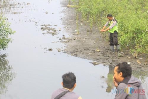 Polisi menunjukkan lokasi penemuan mayat (foto: Agus Salam/ JatimTIMES)
