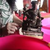 Patung dewa Kong Cho Kong Tik Tjun Ong saat dimandikan oleh salah satu pengurus Klenteng Hong San Kiong. (Foto : Adi Rosul / JombangTIMES)