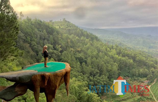 Salah satu pengunjung sedang swafoto di spot foto pulau melayang Kampung Papua, Goa Pinus, Dusun Brau, Desa Gunungsari, Kecamatan Bumiaji. (Foto: Irsya Richa/BatuTIMES)