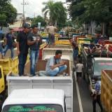 Sejumlah sopir dump truck berada di atas truk yang terparkir di ruas Jl A. Yani, Banyuwangi.