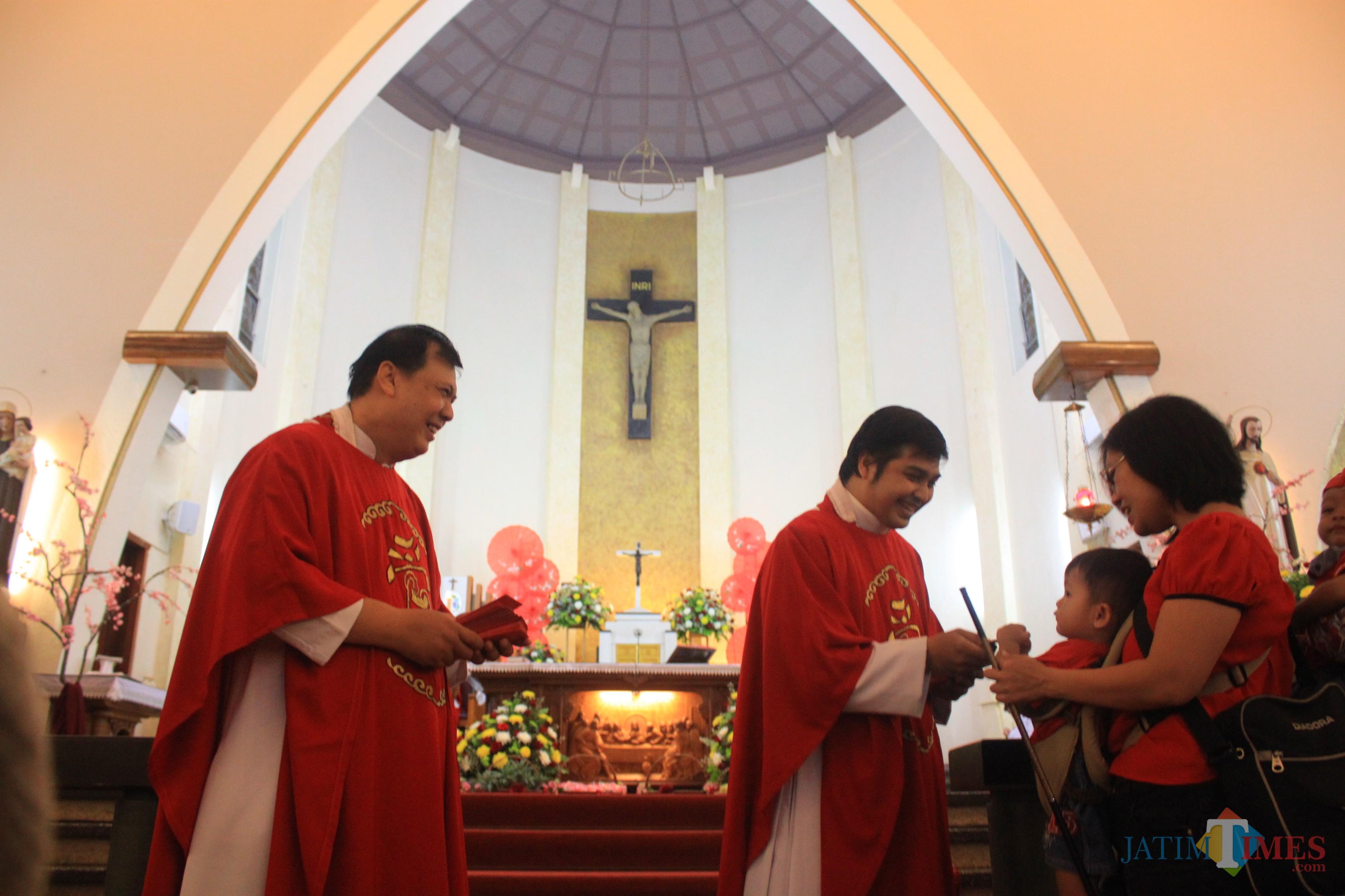 Pastor Gereja Katerdal Ijen bagikan Angpao kepada jemaat anak - anak