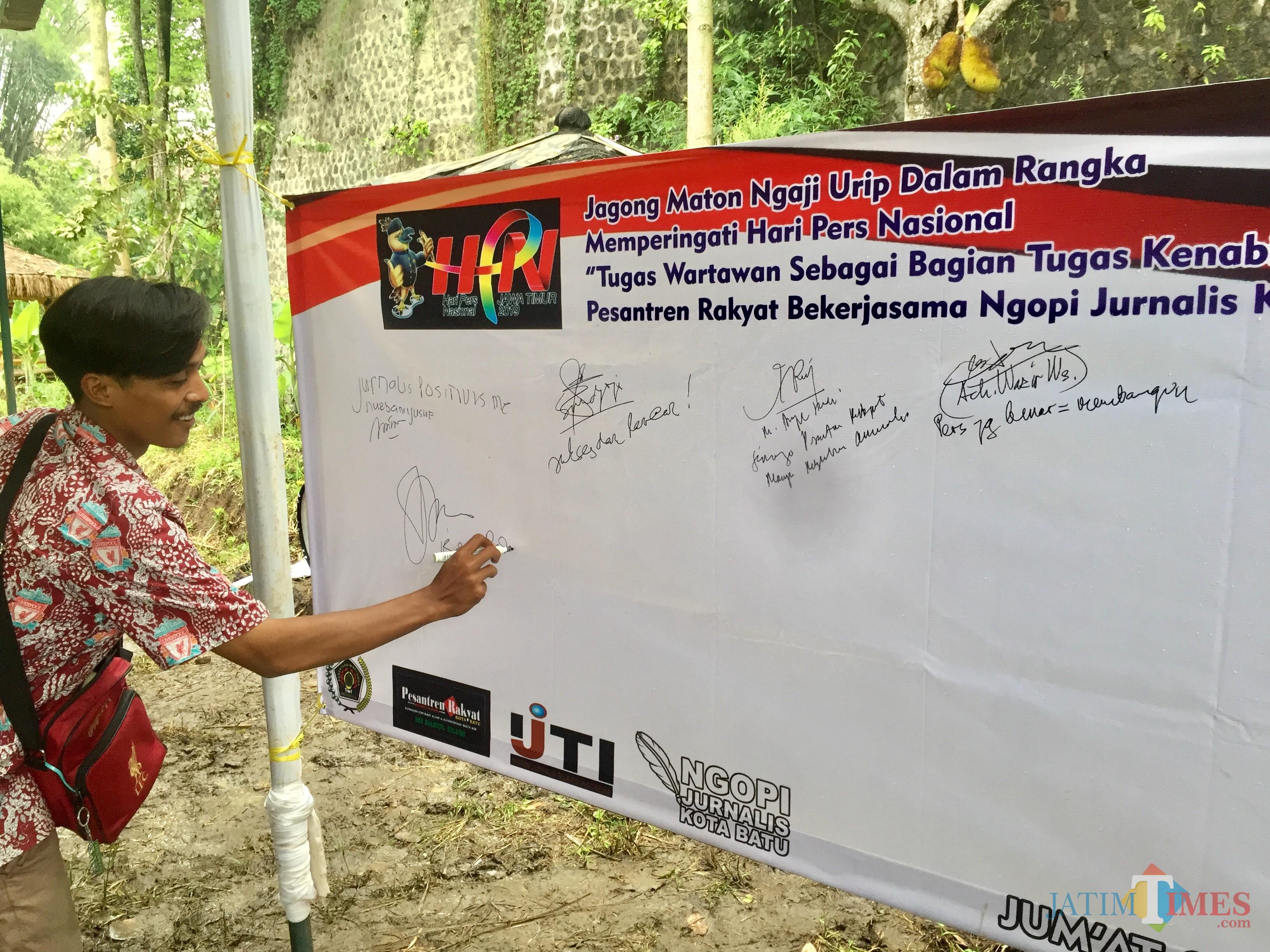 Salah satu wartawan menandatangani komitmen di HPN 2019 diPesantren Rakyat Kota Batu Kawasan Edukasi Alam & Konservasi Sumber Mata Air MI Darul Ulum, Dusun Macari, Desa Pesanggrahan, Kecamatan Batu, Jumat (8/2/2019). (Foto: Irsya Richa/MalangTIMES)