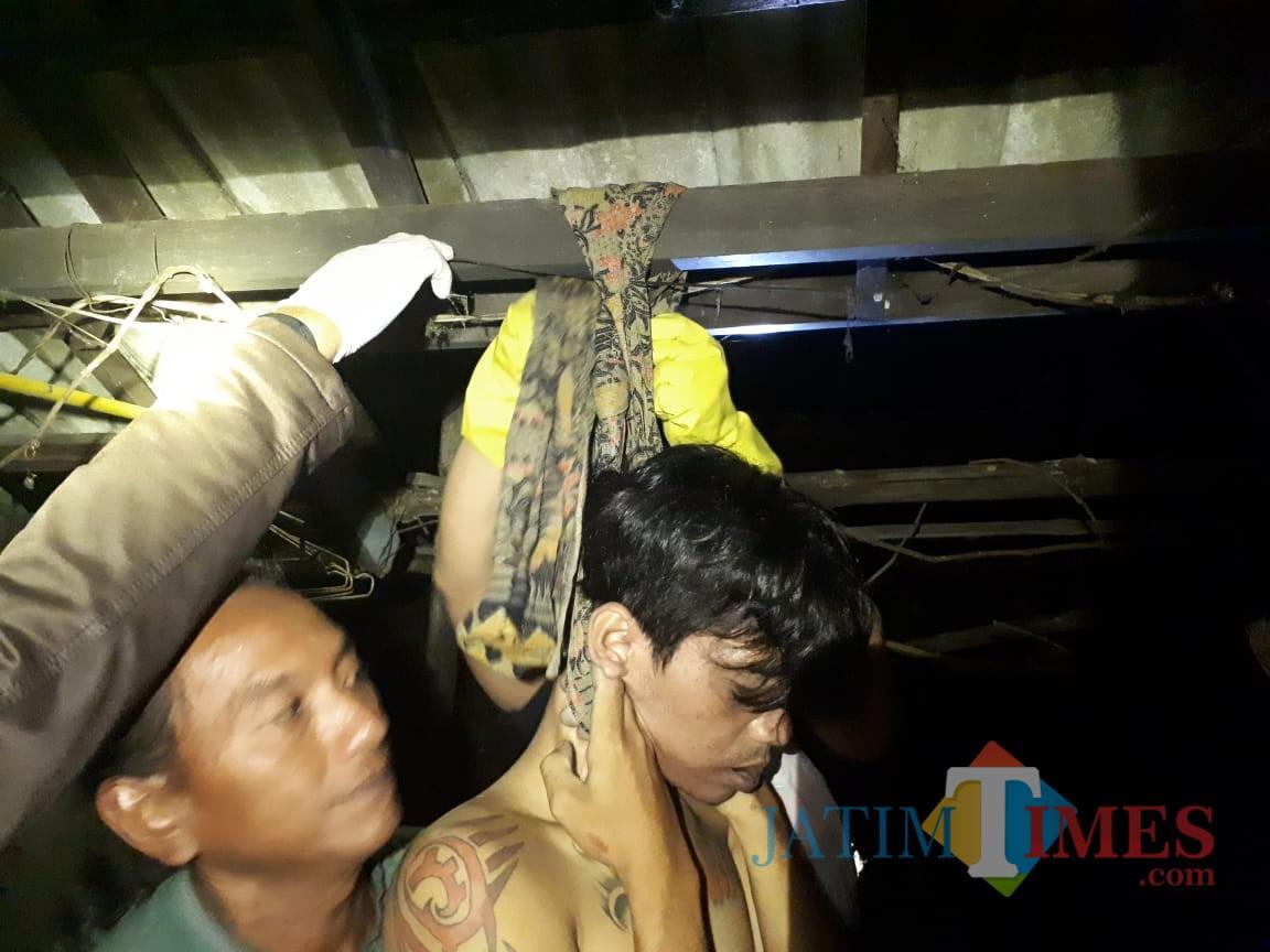 Polisi menurunkan jasad E dari kain yang digunakan gantung diri (Foto : Ist/Humas Polres Blitar Kota)