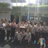Anggota PWI Banyuwangi berfoto bersama anggota Polres Banyuwangi  usai menerima kue ulang tahun
