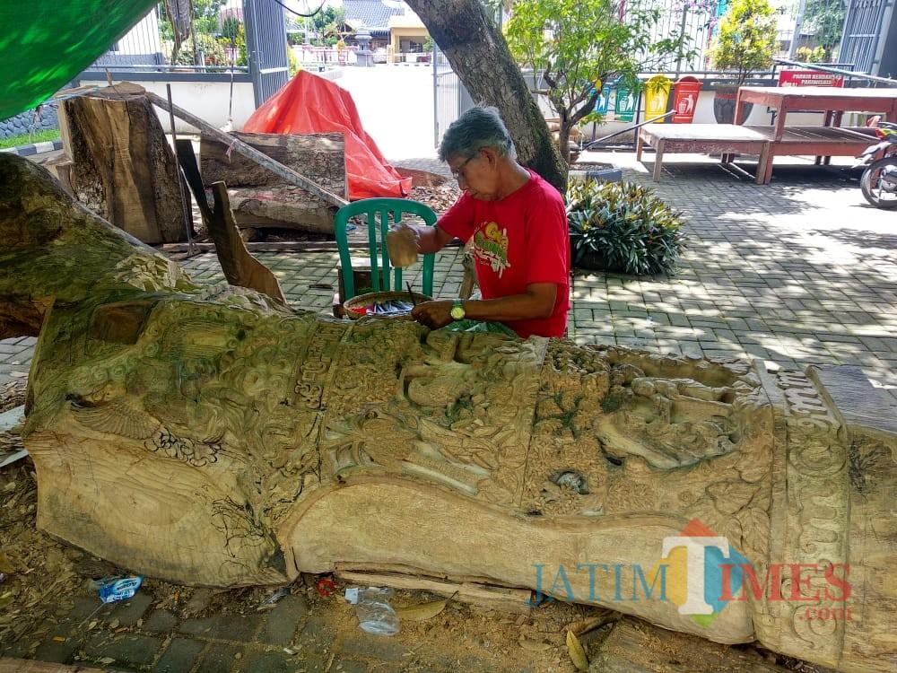 Nampak seniman sedang memahat pohon gada di Istana Gebang (Foto : Team BlitarTIMES)