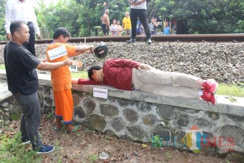 Dalam rekonstruksi, tersangka Wahyudi kepruk helm sebelum letakkan tubuh Ichwan di rel kereta api (Foto : Dokpol/ TulungagungTIMES)