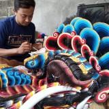 Putut saat mengecat barongan yang dibuatnya sebelum dikirim ke pemesan (foto:  Joko Pramono/Jatim Times)