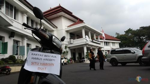 Bentuk protes warga terhadap rencana pengadaan kendaraan dinas bagi DPRD Kota Malang yang ditempel di salah satu roda dua yang terparkir di Balai Kota Malang (Pipit Anggraeni/MalangTIMES).