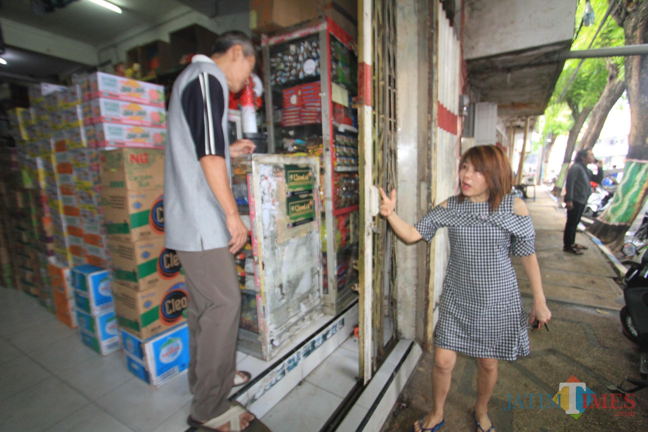 Thia pemilik toko menunjukkan pintu yang dibobol maling  (Agus Salam/Jatim TIMES)