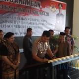 Kapolres Banyuwangi AKBP Taufik Herdiansyah Zeinardi menandatangani piagam pencanangan zona integritas untuk meraih WBBM.
