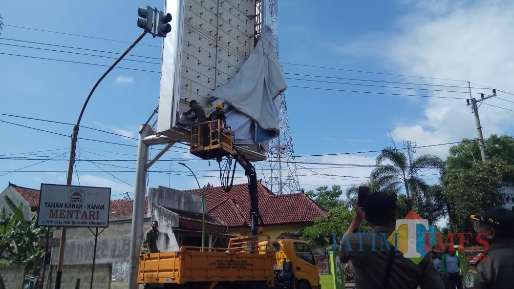 Petugas Satpol PP dan Bawaslu membuka APK yang terpasang di sekitar patung kuda, Karangente Banyuwangi.