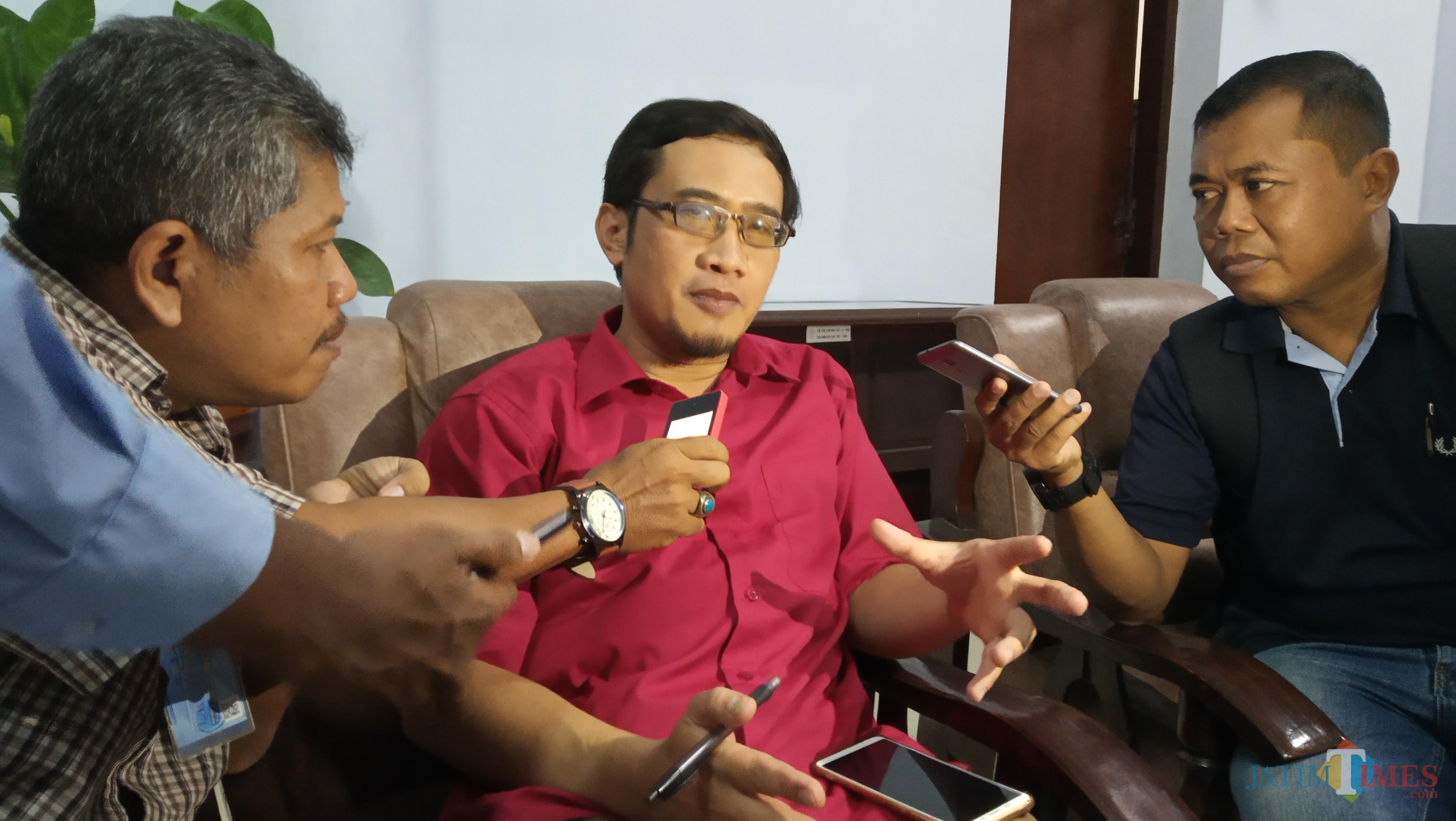 Timour (baju merah) saat diwawancarai oleh awak media. (foto : Joko Pramono/Jatim Times)