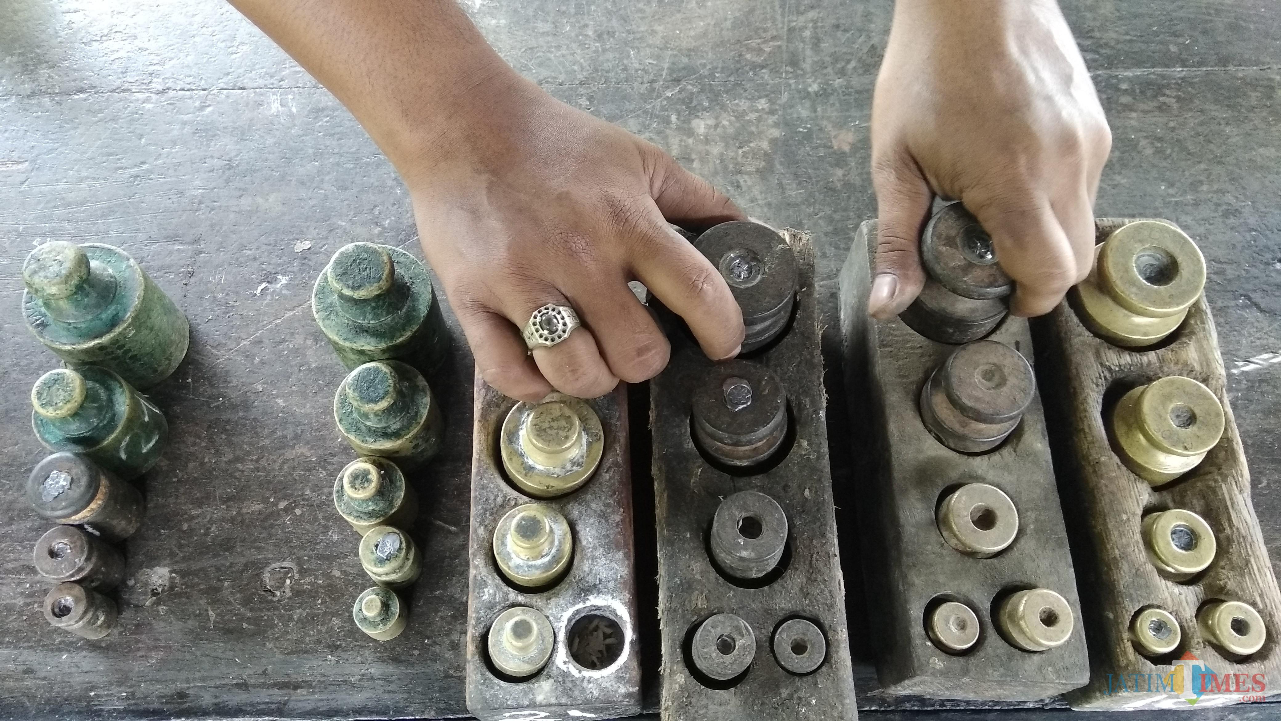 Petugas Disdag Kota Malang mengecek anak timbangan yang digunakan para pedagang pasar tradisional. (Foto: Nurlayla Ratri/MalangTIMES)