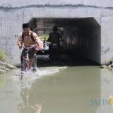 Seorang pelajar saat terlihat melintas Underpass Tol Jombang-Mojokerto di Desa Kedungbetik, Kecamatan Kesamben, Kabupaten Jombang yang lagi tergenang air. (Foto : Adi Rosul / JombangTIMES)