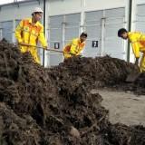 Para petugas kebersihan di TPA Supit Urang tengah mengeruk kompos kering siap kemas. (Foto: Nurlayla Ratri/MalangTIMES)