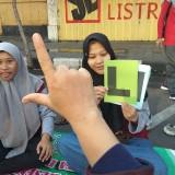 Salah satu pengunjung stand sedang belajar bahasa isyarat. (Eko Arif S /JatimTIMES)