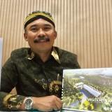 Kepala Desa Tulungrejo Suiyono menunjukkan desain wisata petik apel di kantornya. (Foto: Irsya Richa/MalangTIMES)