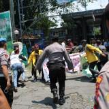 Sejumlah mahasiswa berlarian saat kericuhan unjuk rasa mahasiswa Undar dengan aparat kepolisian di depan gerbang masuk kampus sisi timur. (Foto : Adi Rosul / JombangTIMES)