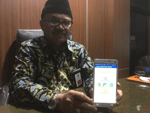 Kepala Badan Pendapatan Daerah (Bapenda) Kabupaten Malang Purnadi, saat menunjukkan aplikasi pembayaran pajak berbasis online yang bisa diunduh melalui play store (Foto : Ashaq Lupito / MalangTIMES)