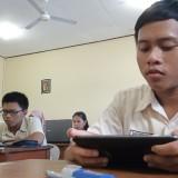 Salah satu siswa yang ikut ujian memakai telepon pintar (foto: Joko Pramono/Jatimtimes)