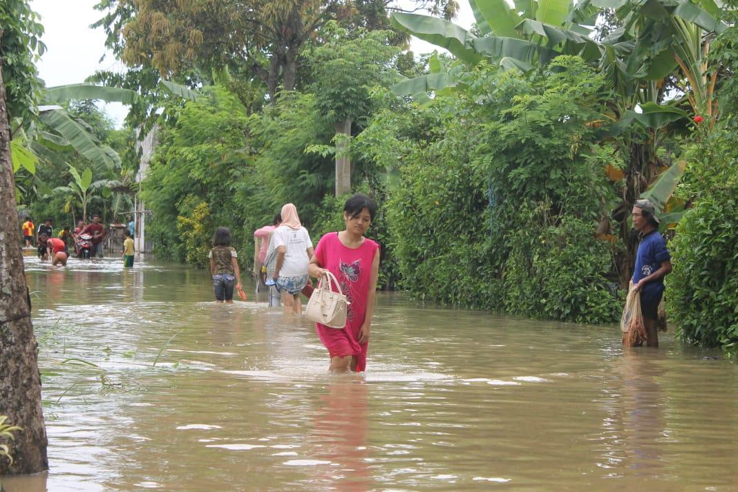 Salah satu warga melintas di jalanan yang tergenang banjir. (foto:  istimewa)