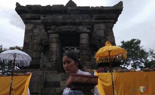 Salah satu umat Hindu asal Kota Malang tengah membawa sesaji untuk upacara Ngembak Geni di Candi Badut. (Foto: Nurlayla Ratri/MalangTIMES)