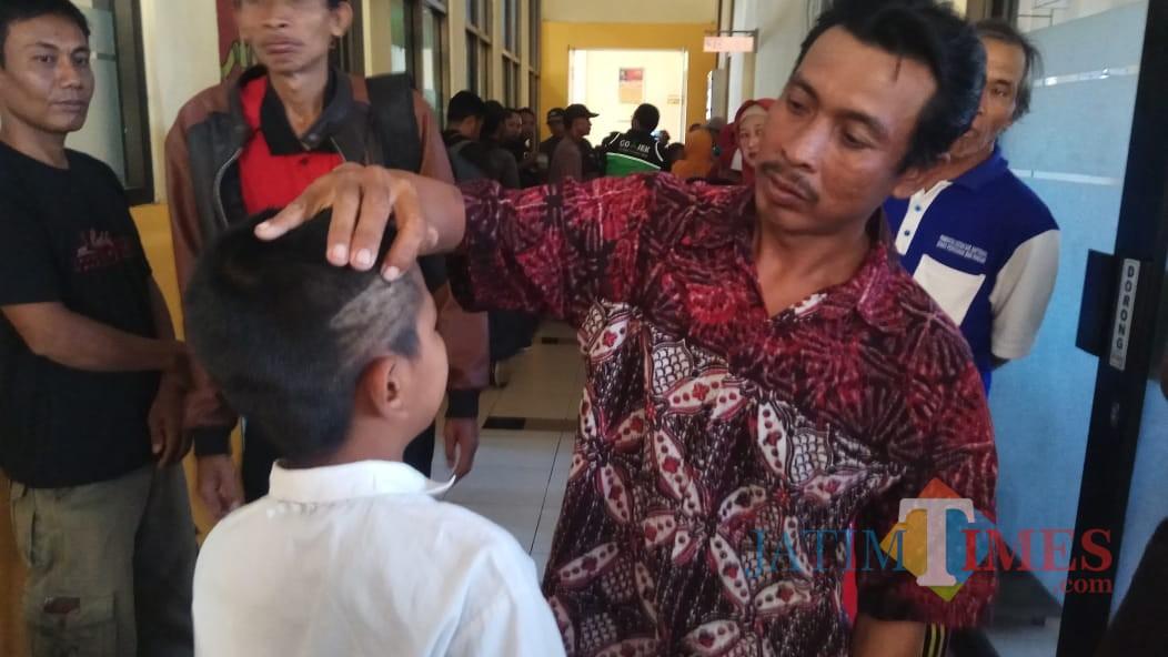 Orang tua NS menunjukan kepala anaknya yang terluka akibat rambutnya dipotong dengan tidak beraturan