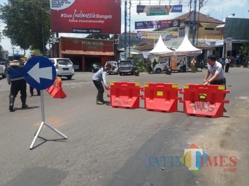 Para petugas Dishub Kota Malang tengah memasang pembatas jalan di bundaran Jalan Bandung. (Foto: Dokumen MalangTIMES)