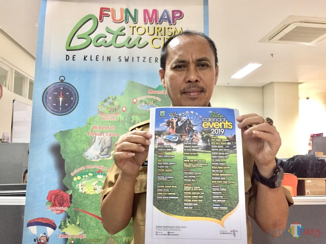 Plt Kepala Dinas Pariwisata Kota Batu Imam Suryono menunjukkan kalender even Kota Batu di kantornya Balai Kota Among Tani. (Foto: Irsya Richa/MalangTIMES)