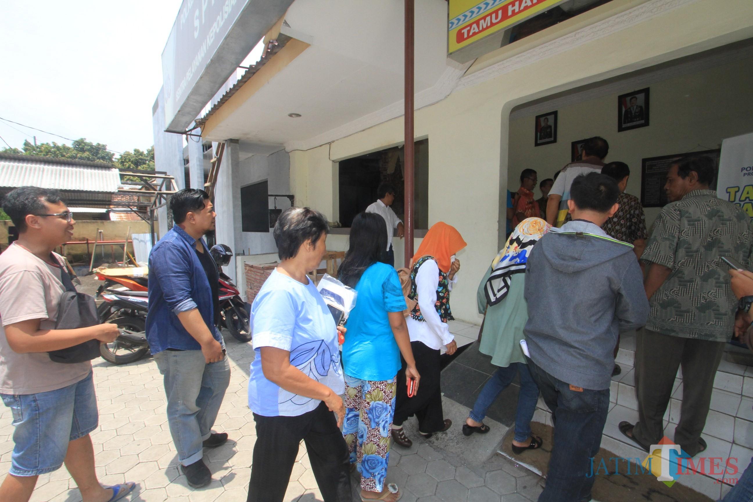 Abdul Wahab dan rekan bersama puluhan kliennya saat melapor ke Polresta Probolinggo (Agus Salam/Jatim TIMES)